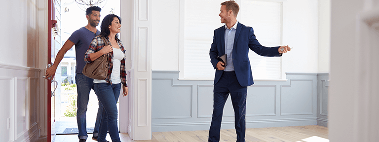 Man and Woman Touring a House with Real Estate Agent